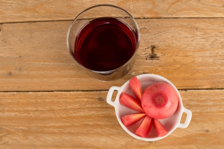 Glass of red wine served with  pickled red onions photo