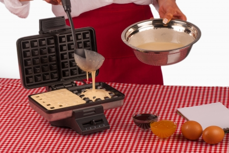 Laddle working with fresh dough to prepare Belgian waffles photo