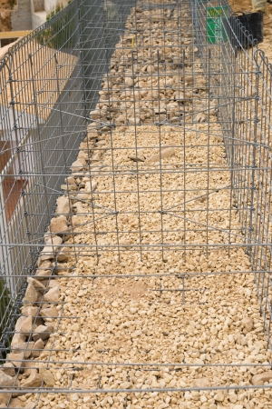 Unfinished gabion cage being filled with stone photo