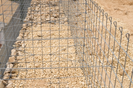 gabion: Gabion cage under construction with the wire mesh being filled with stone