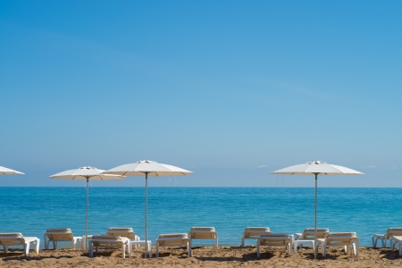 sunshades: Deckchairs and sunshades waiting for  sun hungry holidaymakers
