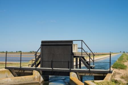 sluice: Irrigation gate amidst the rice fields of Ebro delta, Tarragona, Spain