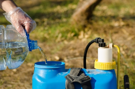 pesticide: Protected hands filling a pesticide sprayer Stock Photo
