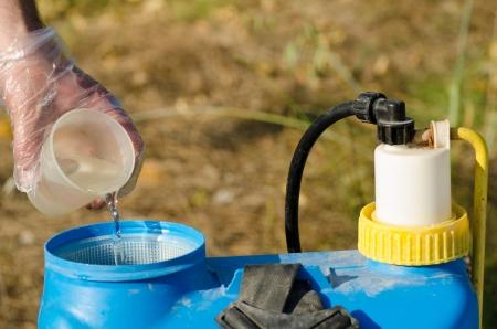 pulverizador: Plaguicidas que se añade en un pulverizador con una taza de medir