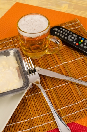 frozen food: Remote control and frozen food, a typical bachelor evening meal Stock Photo