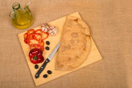 Freshly homemade calzone on a chopping board surrounded by ingredients photo