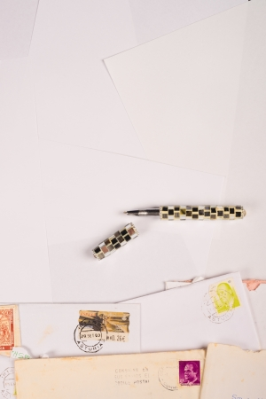 A stack of letters and white writing paper, a background photo