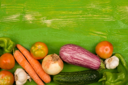 Fresh vegetables arranged on a rustic green table photo