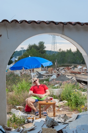 housing crisis: Housing crisis in a humorous concept, guy sunbathing surrounded by rubble Stock Photo