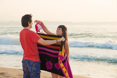 changing clothes: Chica cambia de ropa en la playa y las burlas a su novio Foto de archivo