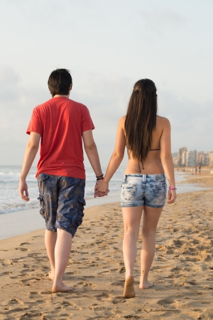 Couple walking on  a lonely beach holding hands photo