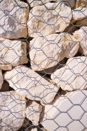 Detail take of stones behind the mesh of a gabion wall photo