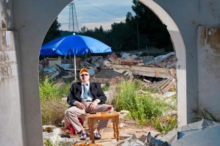 mafioso: Guy sunbathing in depressive surroundings, an economic crisis concept