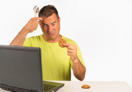 Guy trying to uninstall cookies, a computer dummy concept Stock Photo