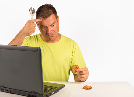 computer user: Guy trying to uninstall cookies, a computer dummy concept Stock Photo