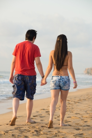 Couple walking on  a lonely beach holding hands Stock Photo