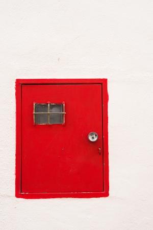 contador electrico: Puerta roja por un medidor de electricidad en una pared encalada Foto de archivo
