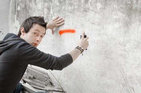 Graffiti artist about to start spraying a wall, looking at camera
