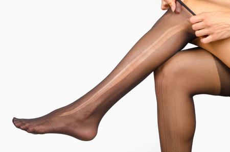 torn stockings: Female legs with a ripped pantyhose on
