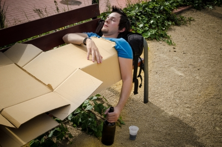 Guy sleeping off a tough hangover on a park bench photo
