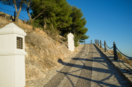 viacrucis: Traditional calvary under Mediterranean sunlight winding uphill towards a cemetry