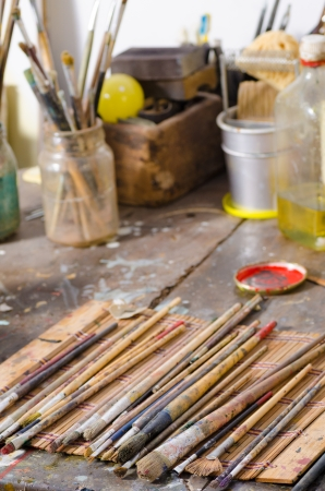 atelier: Many paintbrushes on a messy atelier table Stock Photo