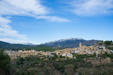caped: Mediterranean village surrounded by snow caped mountains