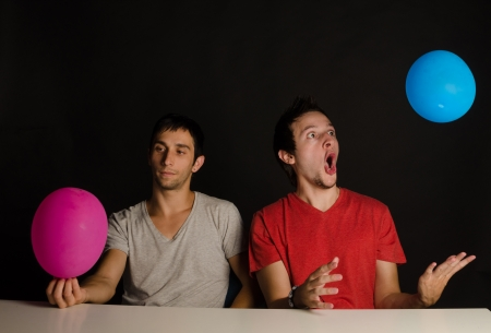 fooling: Two immature guys fooling around with balloons Stock Photo