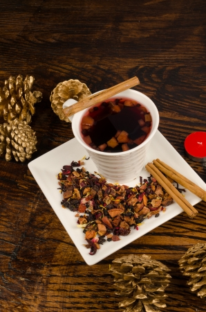 cinammon: Hot fruity tea with cinammon sticks surrounded by Christmas decoration Stock Photo