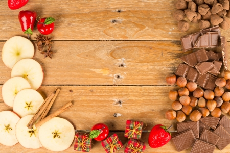 food; background; holiday; seasonal; autumn; Christmas; table; wooden; rustic; old; copy space; apples; fir cones; decoration; decorated; sliced; fresh; fruit; cinnamon; nuts; hazelnuts; truffles; chocolate; sweet; candy; treat; aromatic; scented; cinnamo