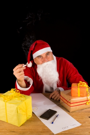 Tired and frustrated Santa smoking a cigarette photo