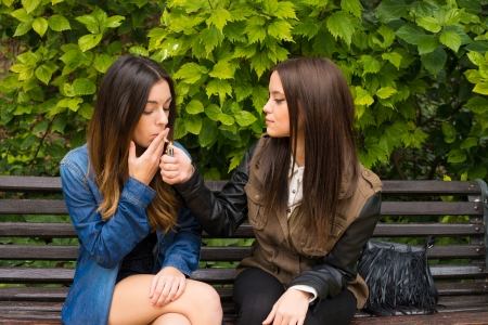 Girls sharing a cigarette on a park bench photo
