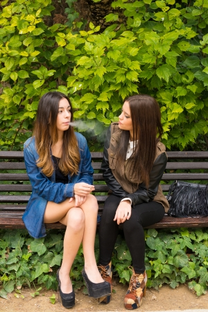 Female couple sharing a cigarette on  a park bench photo