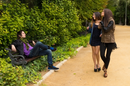 Young women blowing a kiss to  a guy on a park bench