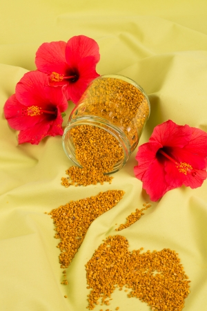 Bee pollen still life with some red flowers photo