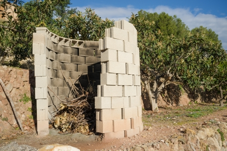 waste prevention: Simple concrete structure to safely burn pruning waste Stock Photo