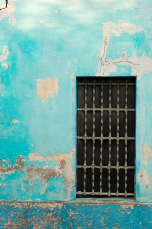 Old window  on a weathered blue Mediterranean facade photo