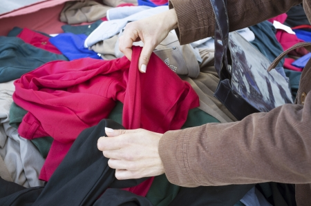 jumble: Femal hands rummaging on a second hand clothes stall