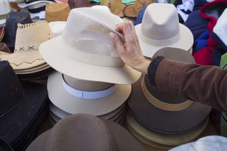 market stall: Female hands choosing a hat on a street market stall Stock Photo