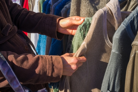 Femal hands rummaging on a second hand clothes stall photo