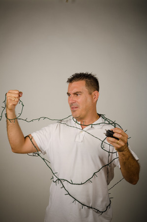 Guy trapped in the wires of festive lights decoration photo