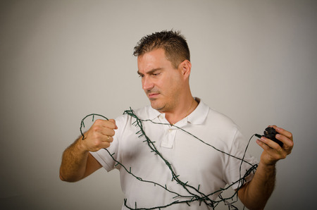 Guy tangled up with the  Christmas tree lights wires photo