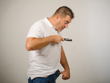 Guy realizing that size maters  and looking into his  trousers Stock Photo