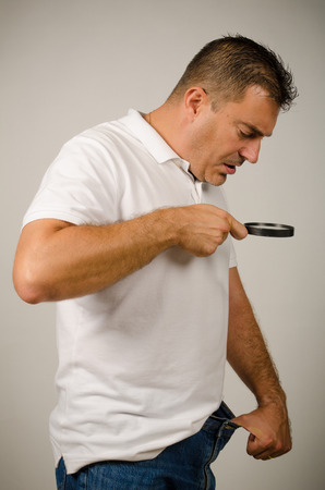 self conceit: Guy having size worries and checking out with a magnifying glass