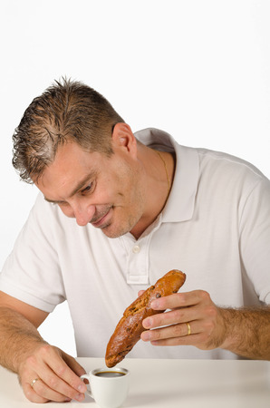 Guy trying to dunk a big roll in an espresso cup Stock Photo