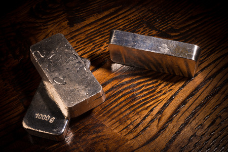 silver bars: Still life with silver bars on a wooden background Stock Photo
