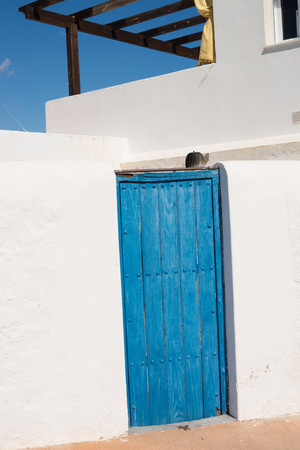 Blue wooden door on a  whitewashed Andalusian facade photo