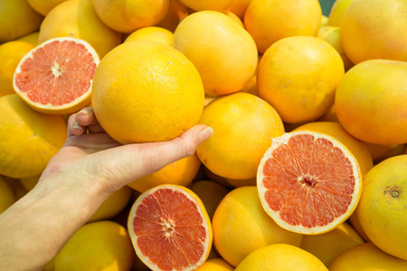 street market: Female hand choosing grapefruit on  a street market stall Stock Photo