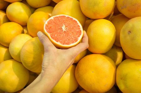 Female hand choosing grapefruit on  a street market stall photo