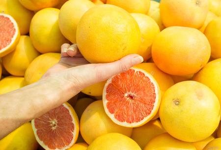 street market: Female hand choosing grapefruit on  a street market stall Stock Photo